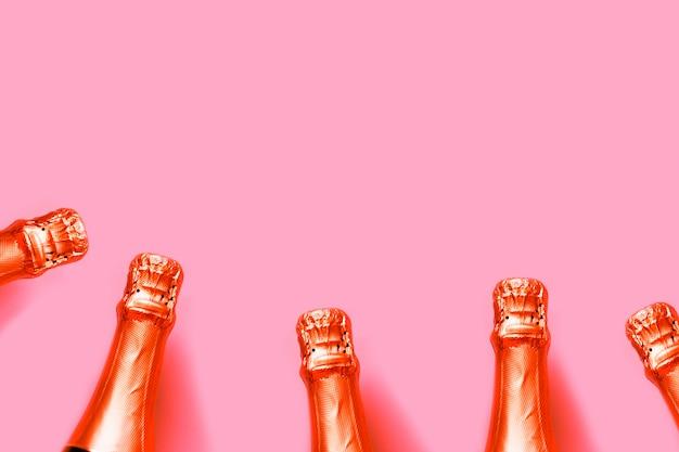Bottiglie di champagne rosso lava fertile su uno sfondo rosa