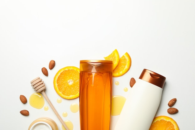 Bottiglie di cosmetici e ingredienti naturali su sfondo bianco