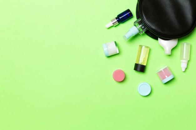 Bottiglie di crema di bellezza cadute dalla borsa dei cosmetici