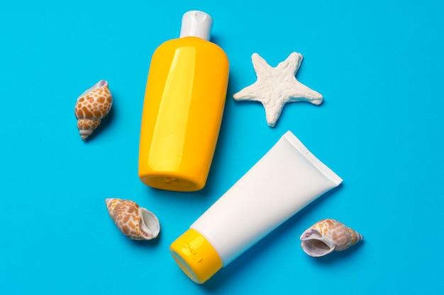 Bottiglie di crema solare con conchiglie di mare su blu, piatto lay