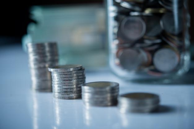 Bottiglie di denaro contante con monete nel concetto di risparmio di denaro