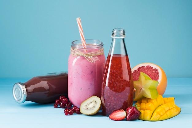 Bottiglie di frullato colorato e frutta