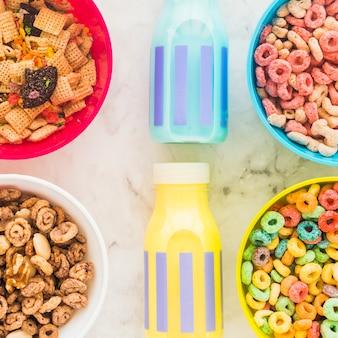 Bottiglie di latte con ciotole luminose di cereali sul tavolo