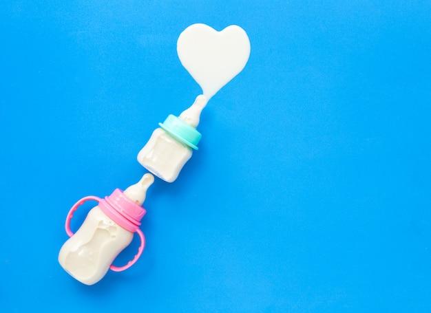 Bottiglie di latte per il bambino sulla superficie blu. forma di cuore di latte