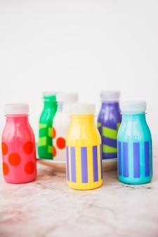 Bottiglie di latte piccole colorate sul piatto