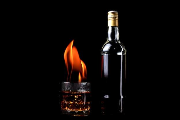 Bottiglie di liquore e bicchiere di whisky con e fiamma di fuoco su sfondo nero