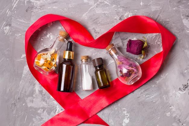 Bottiglie di oli aromatici a forma di nastro di raso rosso a forma di cuore, sale marino, petali di rosa secca e scorza d'arancia per lo scrub