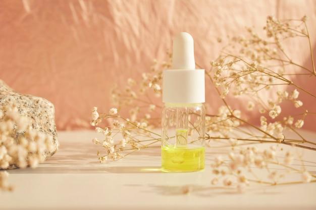 Bottiglie di olio cosmetico essenziale in una bottiglia di vetro su un tavolo bianco. olio per aromaterapia, il concetto di cosmetici naturali.