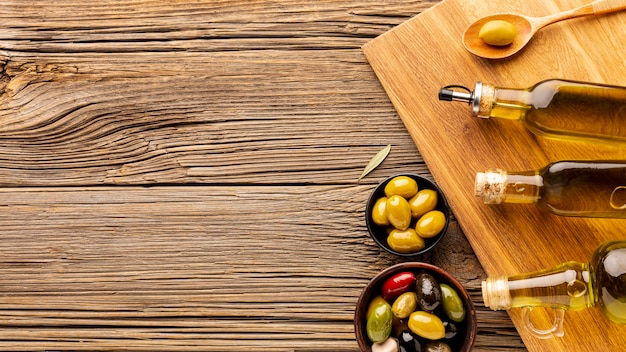 Bottiglie di olio di oliva ciotole e cucchiaio di legno con spazio di copia