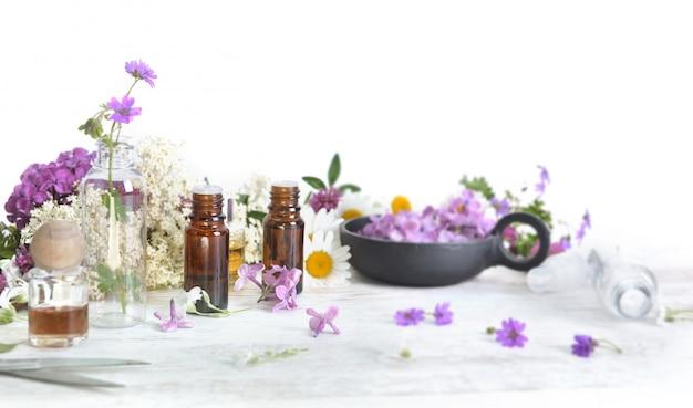 Bottiglie di olio essenziale e petali colorati di fiori di freschezza sul tavolo bianco