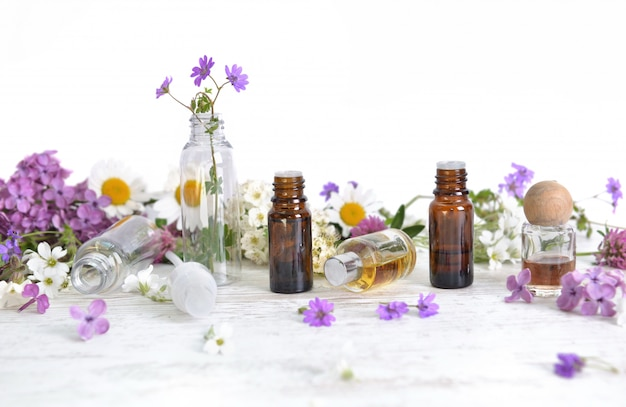 Bottiglie di olio essenziale e petali di fiori colorati sul tavolo bianco
