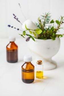 Bottiglie di olio essenziale, sfondo bianco. concetto di cosmetici sani.