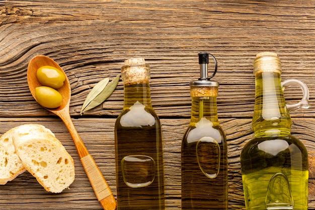 Bottiglie di olio piatto laici e cucchiaio di legno