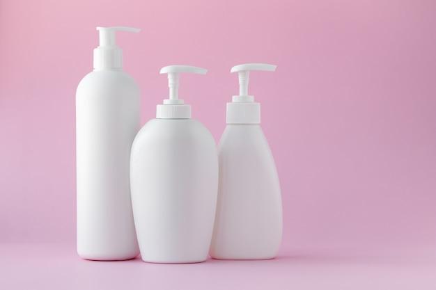Bottiglie di plastica bianche su uno sfondo rosa