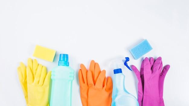 Bottiglie di plastica con guanti e spugna su sfondo bianco