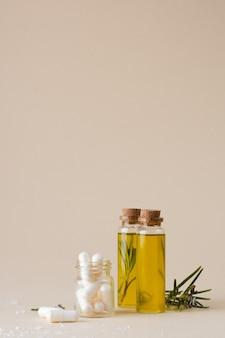 Bottiglie di plastica del primo piano con olio e rosmarino