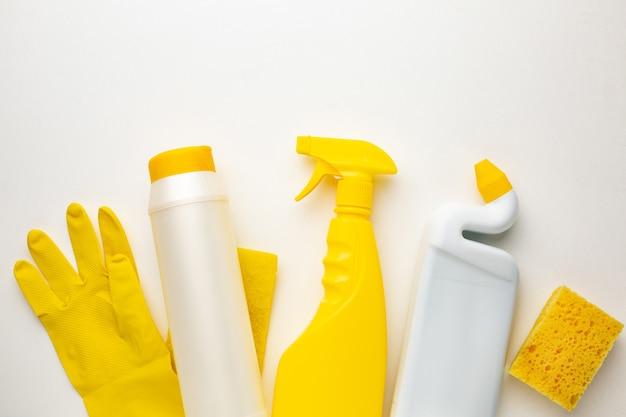 Bottiglie di plastica di prodotti per la pulizia, spugna e guanto su bianco, piatto laici