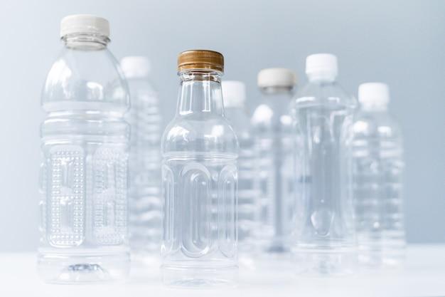 Bottiglie di plastica in varie forme e dimensioni sul tavolo bianco e lo sfondo
