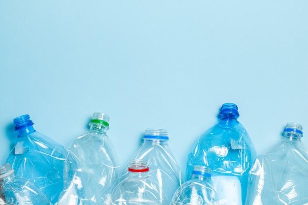 Bottiglie di plastica sgualcite su una priorità bassa blu. rifiuti di plastica.