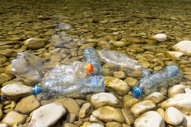 Bottiglie di plastica sporche in acqua