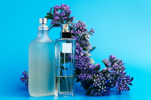 Bottiglie di profumo con i fiori su un azzurro