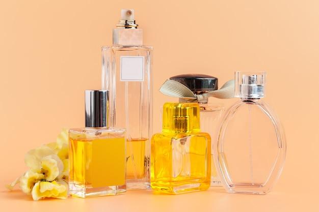 Bottiglie di profumo con i petali di fiori su beige