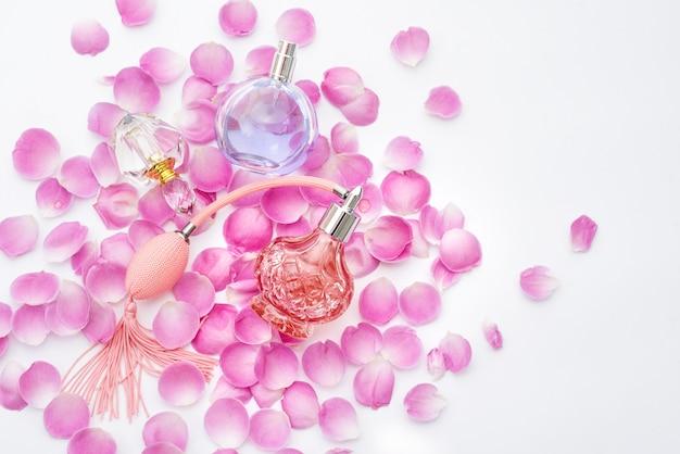 Bottiglie di profumo con petali di fiori. profumeria, cosmetici, collezione di fragranze