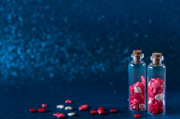 Bottiglie di vetro con zuccherini di zucchero a forma di cuore su sfondo blu glitter. concetto di san valentino, dolce amore.