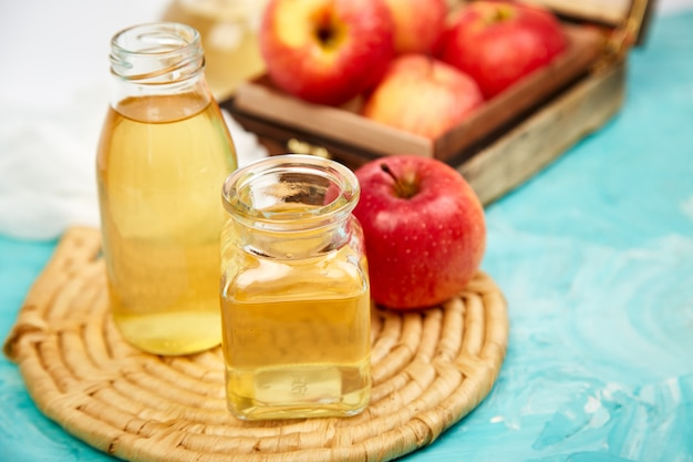 Bottiglie di vetro di aceto di mele biologico e mele rosse