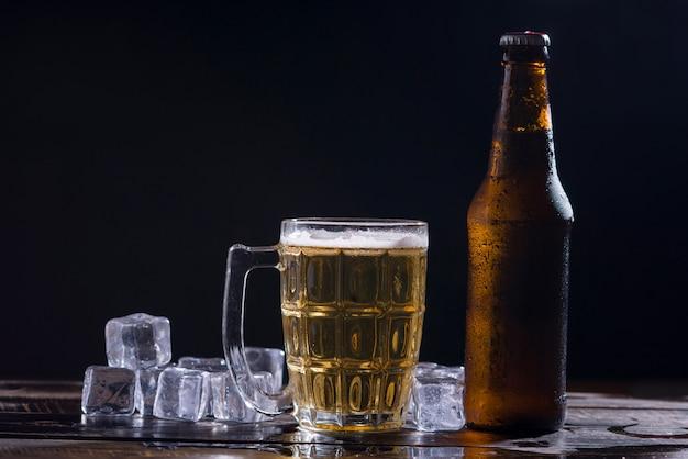 Bottiglie di vetro di birra con vetro e ghiaccio su sfondo scuro