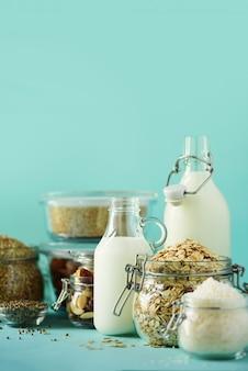 Bottiglie di vetro di latte vegetale vegan e mandorle, noci, cocco, latte di semi di canapa su sfondo blu.