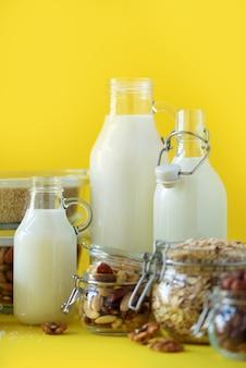 Bottiglie di vetro di latte vegetale vegan e mandorle, noci, cocco, latte di semi di canapa su sfondo giallo.