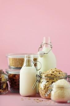 Bottiglie di vetro di latte vegetale vegan e mandorle, noci, cocco, latte di semi di canapa su sfondo rosa.