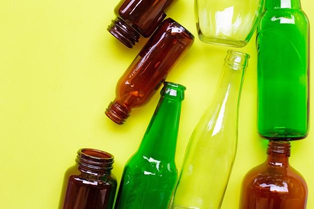 Bottiglie di vetro su sfondo giallo verde.