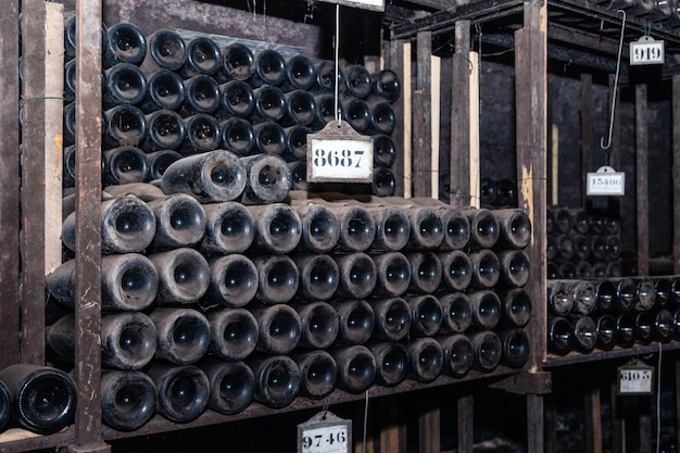 Bottiglie di vino antiche che invecchiano nella cantina sotterranea nelle file
