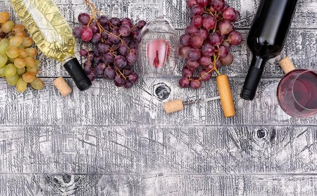 Bottiglie di vino di vista superiore con l'uva e lo spazio della copia sull'orizzontale di legno bianco