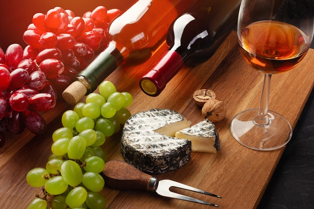 Bottiglie di vino rosso e bianco con grappolo d'uva, testa di formaggio, noci e bicchiere di vino su tavola di legno