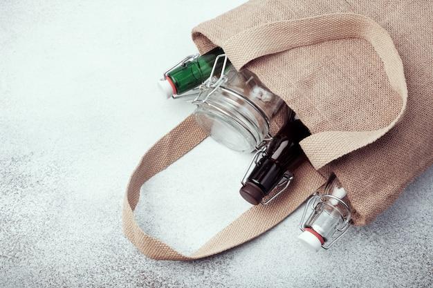 Bottiglie e barattoli di vetro riutilizzabili nel sacchetto di tela. stile di vita sostenibile. concetto di spesa alimentare zero rifiuti