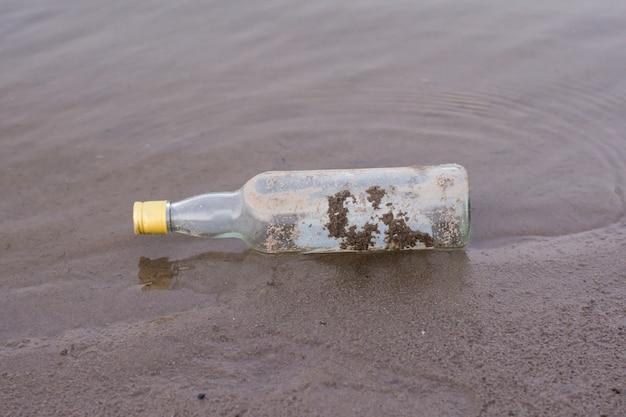 Bottiglie e rifiuti spazzatura sulla riva di un fiume.