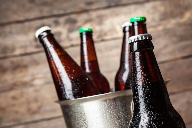 Bottiglie fredde di birra nel secchio sul legno