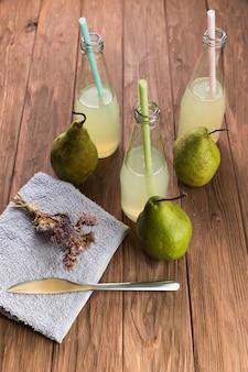 Bottiglie fresche del succo di pera di vista superiore sulla tavola di legno