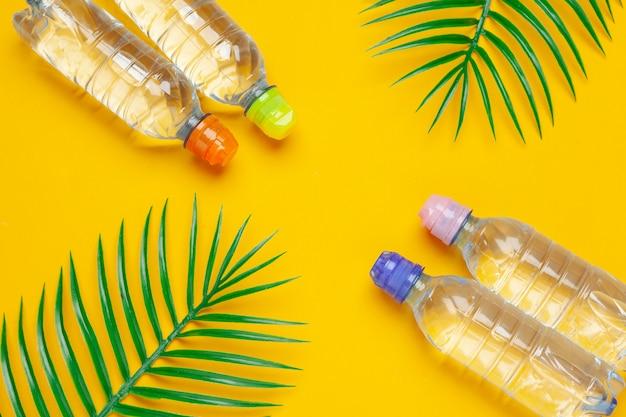 Bottiglie liquide trasparenti con foglie di palma tropicali