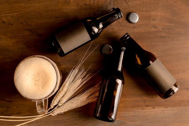 Bottiglie marroni di birra con schiuma di vetro di birra dentro sul tavolo di legno