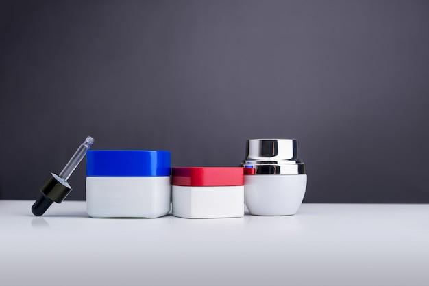 Bottiglie per cosmetici e prodotti di bellezza isolati su grigio