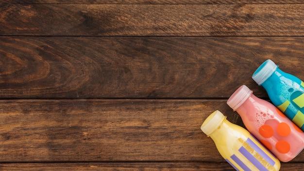 Bottiglie per il latte variopinte sulla tavola di legno