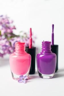 Bottiglie rosa e viola dello smalto su fondo bianco