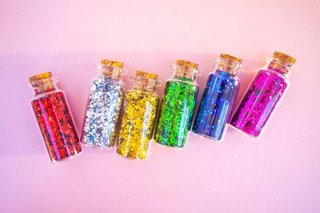Bottiglie trasparenti con lustrini di blu, verde, argento, oro e rosso. perla pastello. vista dall'alto, minimalismo, disteso.