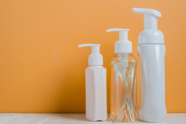 Bottiglie trasparenti e bianche del dispenser del sapone contro un fondo arancio