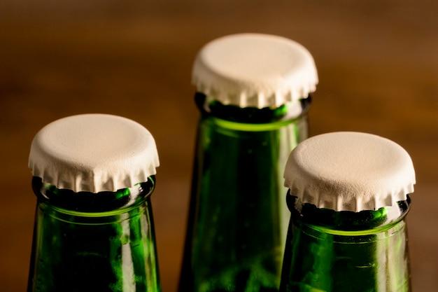 Bottiglie verdi della bevanda alcolica con tappi bianchi