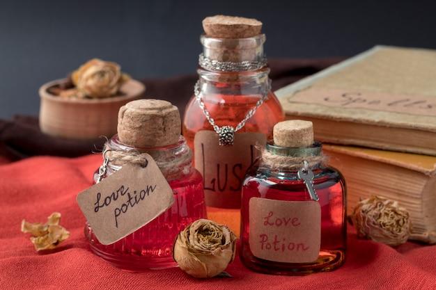 Bottiglie vintage con pozioni d'amore magiche e libri di incantesimi su tessuto rosso
